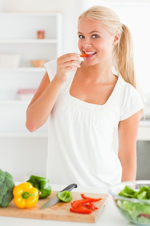 Woman eating a slice of pepper in her kitchen photo