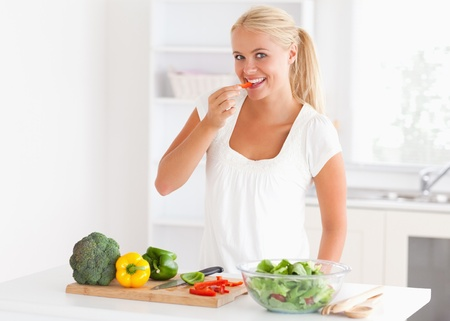 Woman eating pepper in her kitchen photo