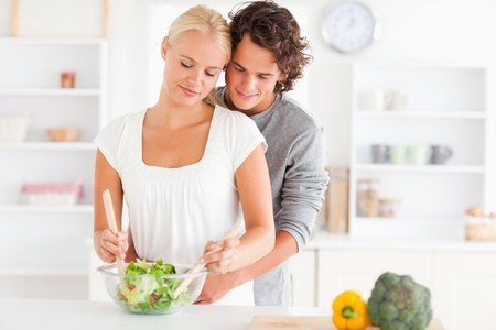 Couple preparing a salad in their kitchen photo
