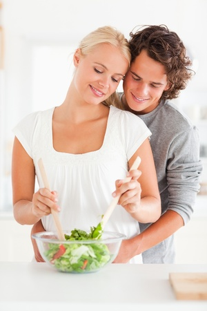 Portrait of a couple preparing a salad in their kitchen photo