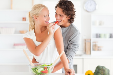 Woman giving pepper to her fiance in their kitchen photo