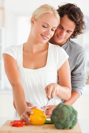 Portrait of a couple slicing pepper in their kitchen photo