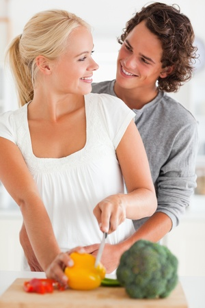 vegetables young couple: Portrait of a smiling couple slicing pepper in their kitchen