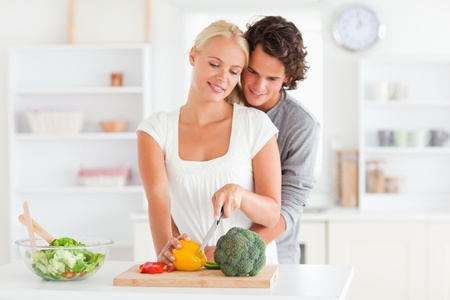 Couple slicing pepper in their kitchen photo