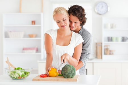 Young couple slicing pepper in their kitchen photo
