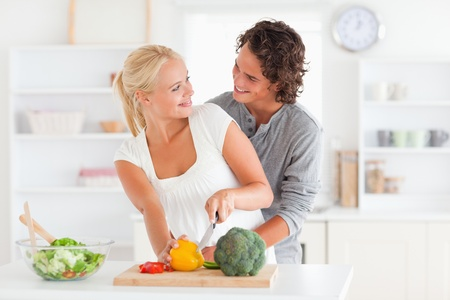 Happy couple slicing pepper in their kitchen photo