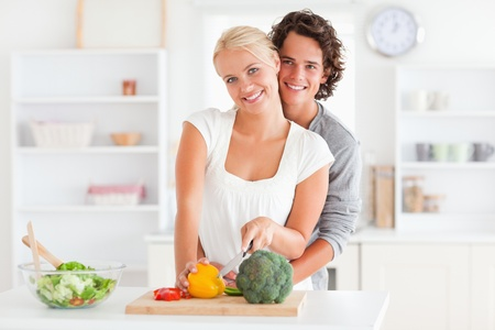 Lovely couple slicing pepper in their kitchen photo
