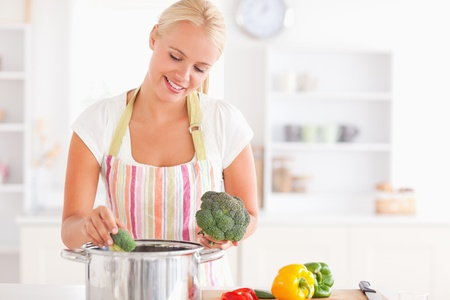 Woman putting cabbage on boiling water while wearing an apron photo