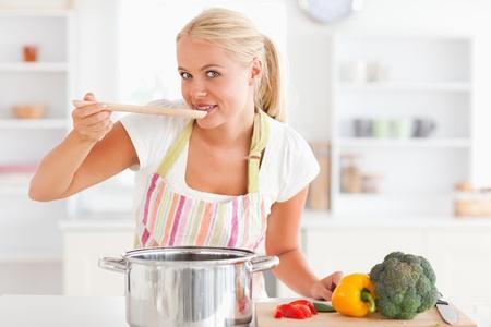 hombre cocinando: Mujer rubia saboreando su comida mientras mira a la c�mara Foto de archivo