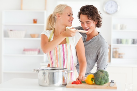 Woman making her fiance tasting her meal while wearing an apron photo