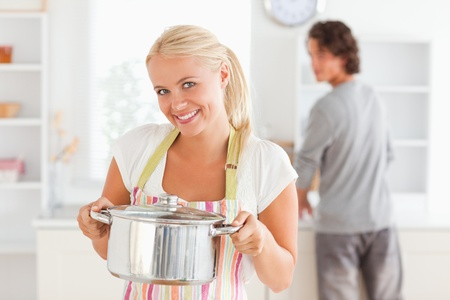 Woman posing with a boiler while her fiance is washing the dishes in their kitchen photo