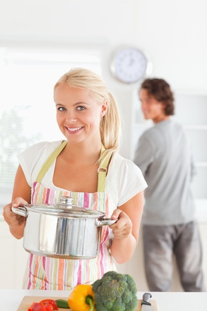 Portrait of a woman posing with a boiler while her fiance is washing the dishes in their kitchen photo