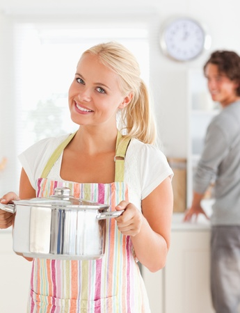 Portrait of a woman posing while her fiance is washing the dishes in their kitchen photo