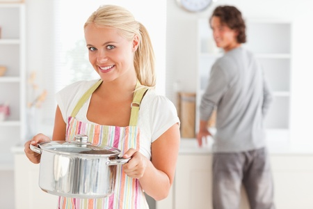 Portrait of a woman posing while a man is washing the dishes in their kitchen photo