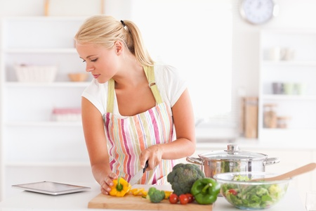 Woman using a tablet computer to cook in her kitchen Stock Photo - 11230890