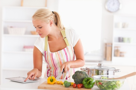 Blonde woman using a tablet computer to cook in her kitchen photo