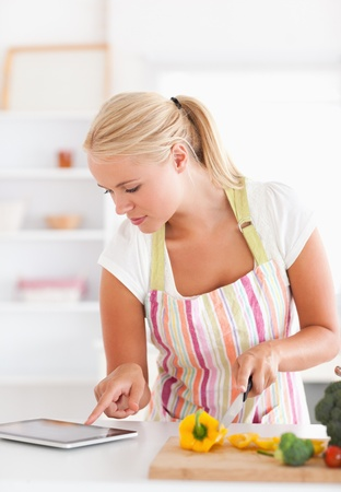 Portrait of a woman using a tablet computer to cook in her kitchen photo