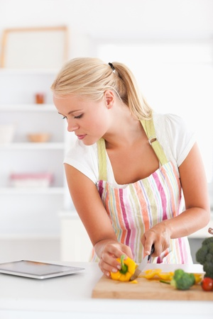 Portrait of a blonde woman using a tablet computer to cook in her kitchen photo