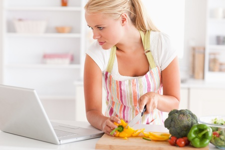 Close up of a woman using a laptop to cook in her kitchen photo