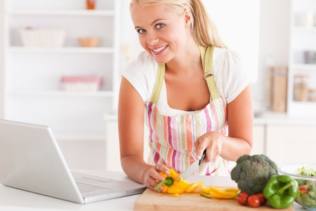 Close up of a blonde woman using a laptop to cook in her kitchen photo