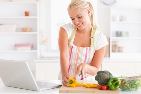 p of a blonde woman using a notebook slicing a pepper in her kitchen photo