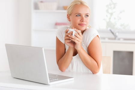 Cute woman having a cup of tea while with a notebook looking away from the camera photo