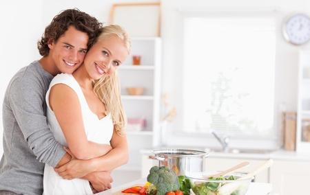 vegetables young couple: Young couple posing in their kitchen