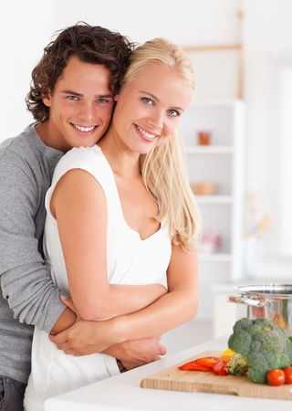 Portrait of a young couple posing in their kitchen photo