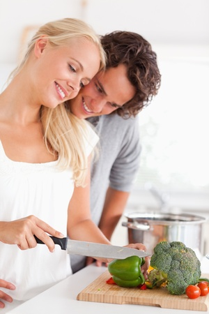 Portrait of a couple chopping pepper in their kitchen photo