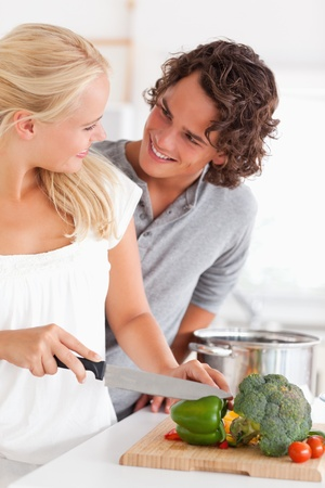 Portrait of a couple cooking while looking at each other photo