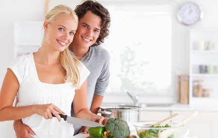 Beautiful couple cooking while looking at the camera photo