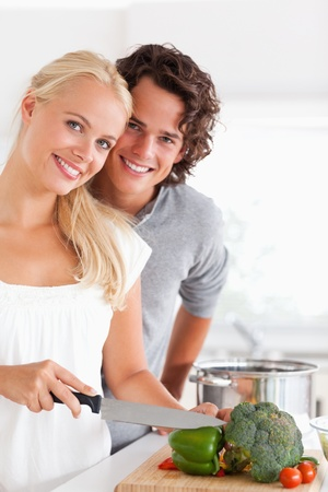 Portrait of a beautiful couple cooking while looking at the camera photo