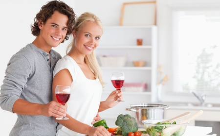 Couple having a glass of wine while cooking photo