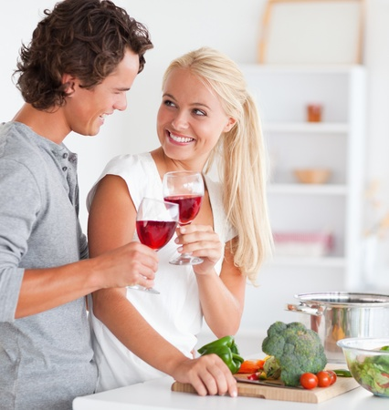 Portrait of a couple having a glass of red wine while cooking photo