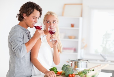 Couple drinking a glass of red wine in their kitchen photo