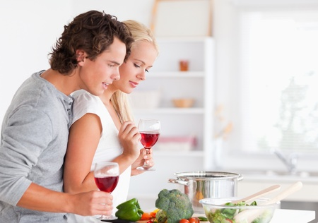 Couple cooking while having a glass of wine in their kitchen photo
