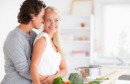 Couple hugging while cooking in their kitchen Stock Photo - 11229278