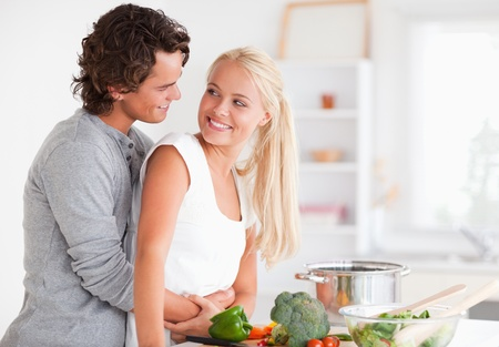 Lovely couple hugging while cooking in their kitchen photo