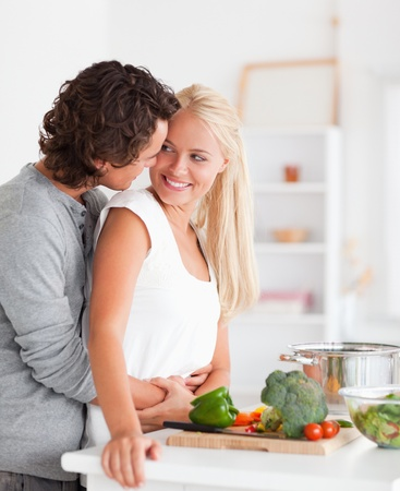 vegetables young couple: Portrait of a couple hugging while cooking in their kitchen