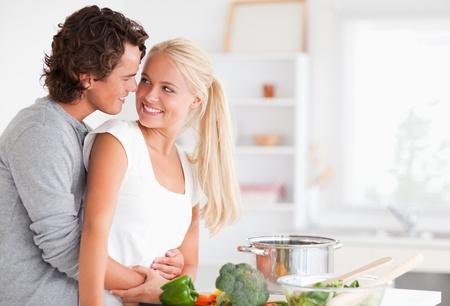 pareja comiendo: En el amor abrazando pareja durante la cocci�n en su cocina