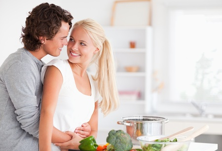 hugging couple: In love couple hugging while cooking in their kitchen