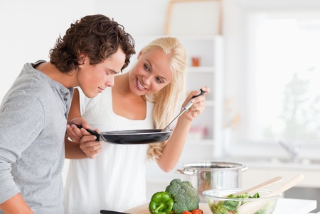 Couple cooking with a pan in their kitchen photo