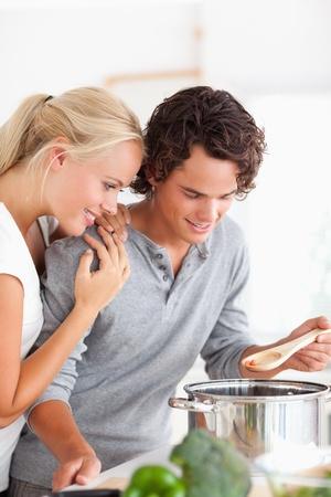 Portrait of a couple tasting a meal in their kitchen photo