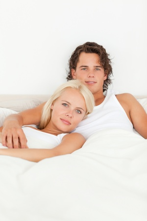 Cute couple lying on a bed while looking at the camera photo