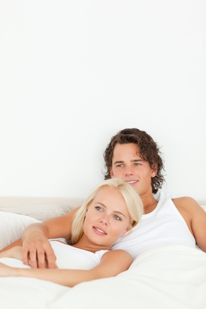 Portrait of a happy couple lying on a bed looking away from the camera photo