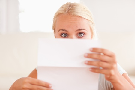 Shocked woman reading a letter in her living room photo