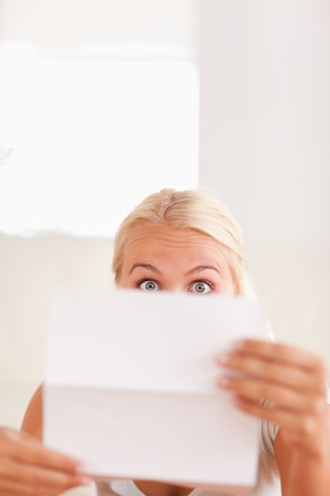 Shocked blond woman reading a letter in her livingroom photo