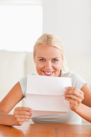 Grinning woman holding a letter in her living room photo