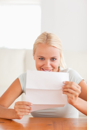 Smiling woman reading a letter in her living room photo