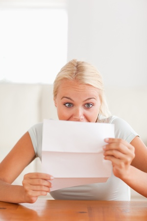 Woman looking at a letter in disbelief in her living room photo
